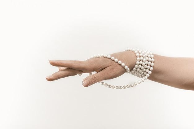 Pareljuwelen op rijpe vrouwelijke hand die op wit wordt geïsoleerd