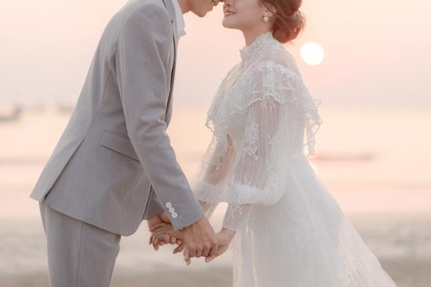 Paren hand in hand en zoenen op het strand door de zee. liefde concept