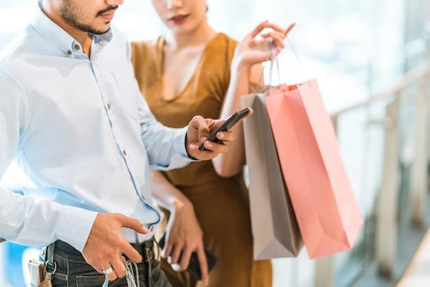 Paren kopen in het winkelcentrum hij gebruikt een telefoon. om het product te bekijken.
