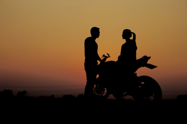Paren met een motorfiets bij zonsondergang