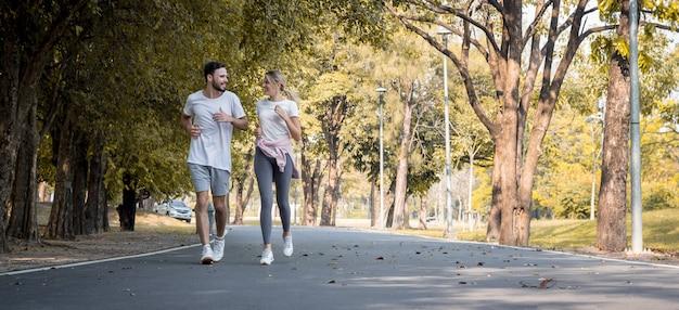 Paren oefenen in het park. jonge paren die in het park joggen. paren rennen op de weg in het park.
