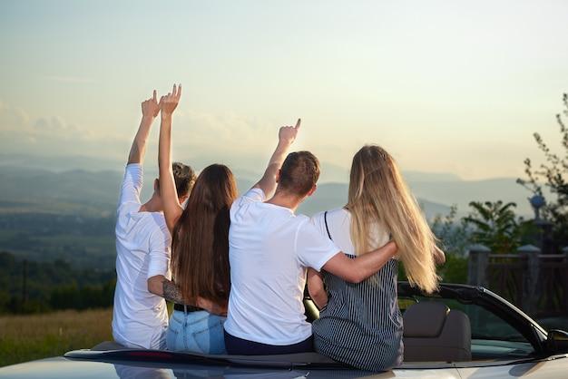 Paren zitten in cabriolet, houden hun handen omhoog en bewonderen een geweldig uitzicht.