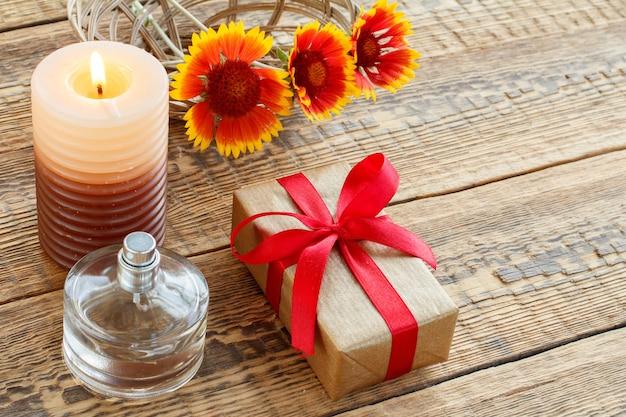 Parfum-, cadeau- of cadeaudoos verpakt in kraftpapier met rood lint, brandende kaars en gele bloemen op houten planken. bovenaanzicht. vakantieconcept.