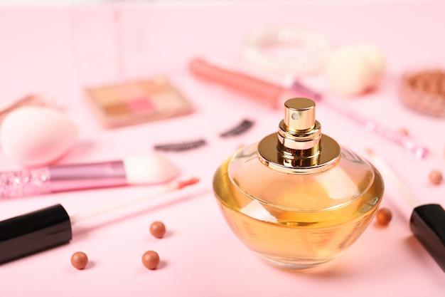 Parfum en decoratieve cosmetica op een roze achtergrond. plaats voor tekst