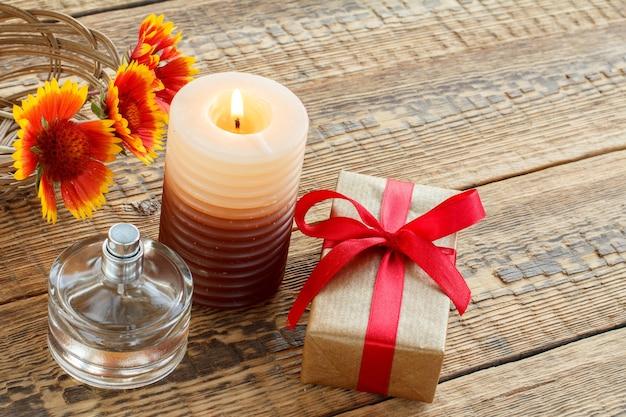 Parfum, geschenkdoos verpakt in kraftpapier met rood lint, brandende kaars en bloemen op houten planken. bovenaanzicht. vakantieconcept.