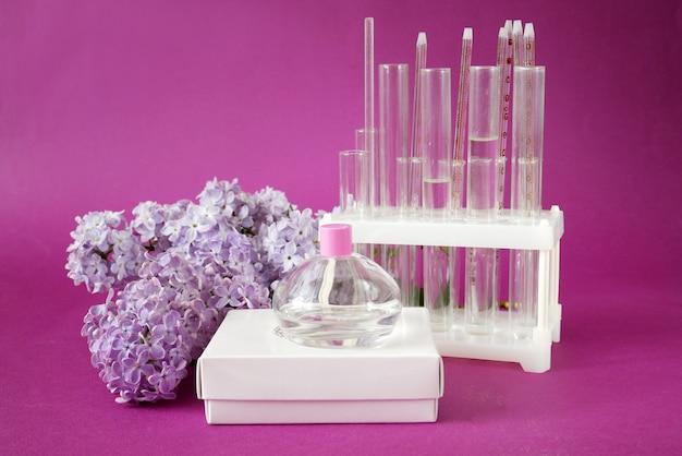 Parfum in fles en lila bloemen achtergrond natuurlijke cosmetische concept
