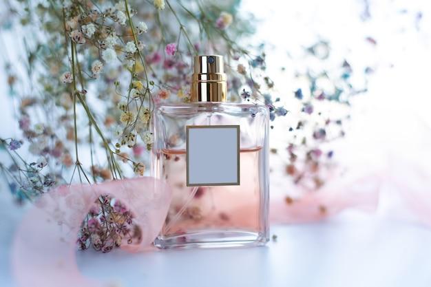 Parfum met bloemen op een lichte achtergrond