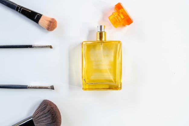 Parfum met gezichtsborstel op witte achtergrond