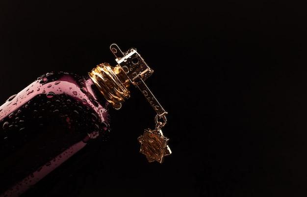 Parfum met waterdruppels op zwart oppervlak