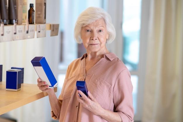 Parfumerie. grijsharige vrouw parfums kiezen in een boetiek