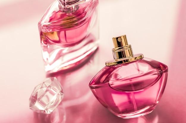 Parfumerie spa en branding concept roze parfumflesje op glanzende zoete bloemengeur glamour geur en eau de parfum als vakantiegeschenk en luxe schoonheidscosmetica merkontwerp