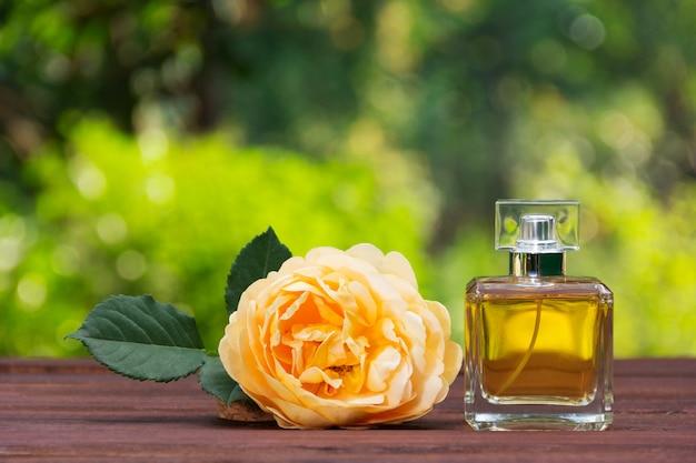 Parfumfles en geurige gele roos.