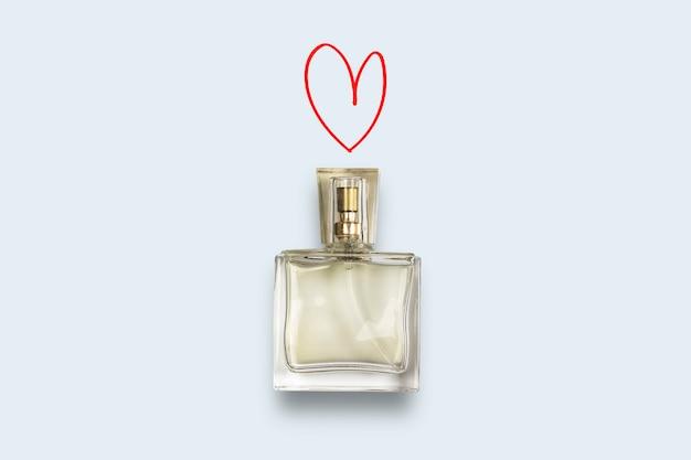 Parfumfles en hart op een blauwe achtergrond. het concept van een favoriete geur, parfum voor de geliefde, feramona. plat lag, bovenaanzicht.