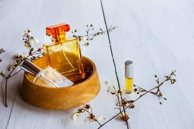 Parfumfles met bloemen op een witte houten achtergrond