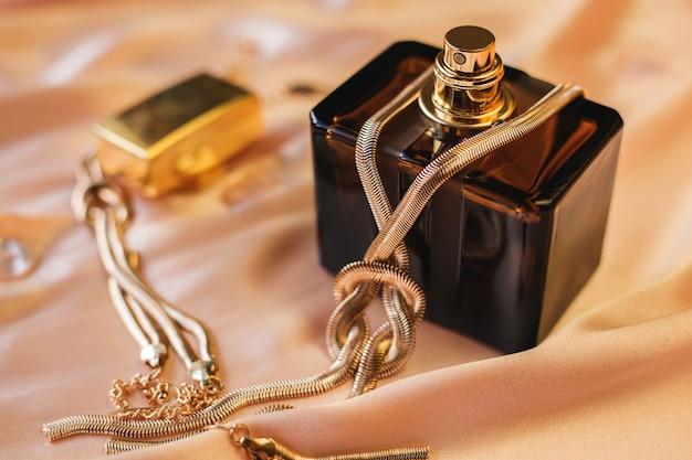 Parfumfles met gouden ketting op roze achtergrond