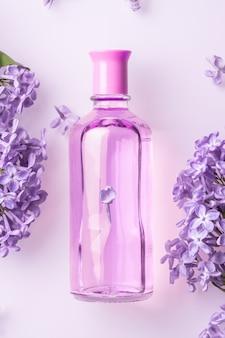 Parfumfles met lila bloemen op witte muur