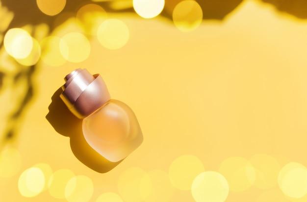 Parfumfles op een gele pastel achtergrond