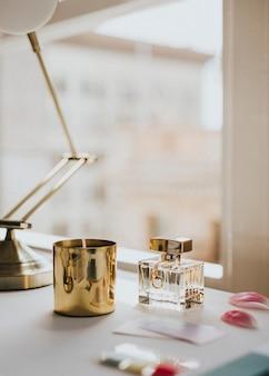 Parfumflesje en een kaars bij een raam