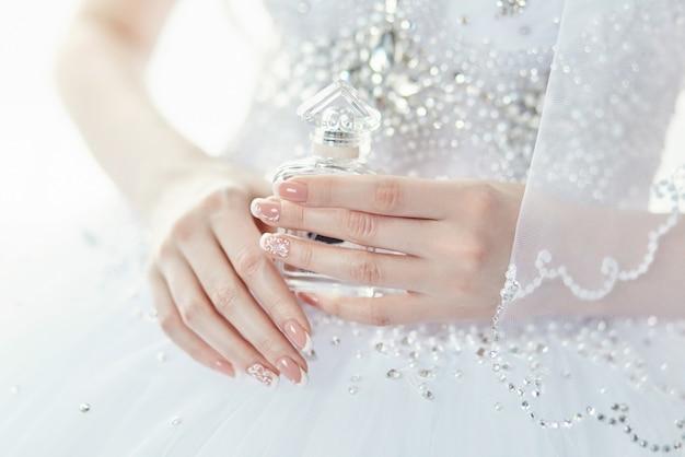 Parfumflesje in de handen van de bruid. een vrouw bereidt zich voor op haar huwelijk. bruid in elegante trouwjurk, mooi verzorgde handen