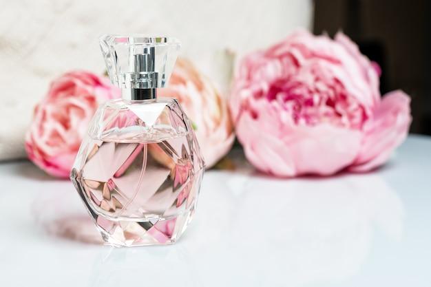 Parfumflesje met bloemen op lichte ondergrond