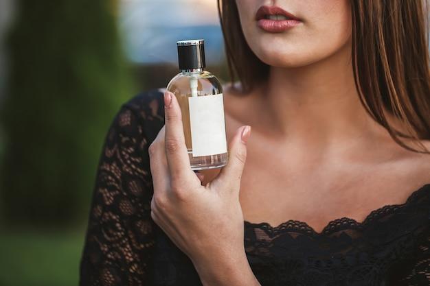 Parfumflesje van een vrouwelijke hand. jonge stijlvolle vrouw met een fles parfum. modieus parfum in de handen van vrouwen. meisje spuiten parfum. mooie vrouwelijke handen. parfums voor vrouwen