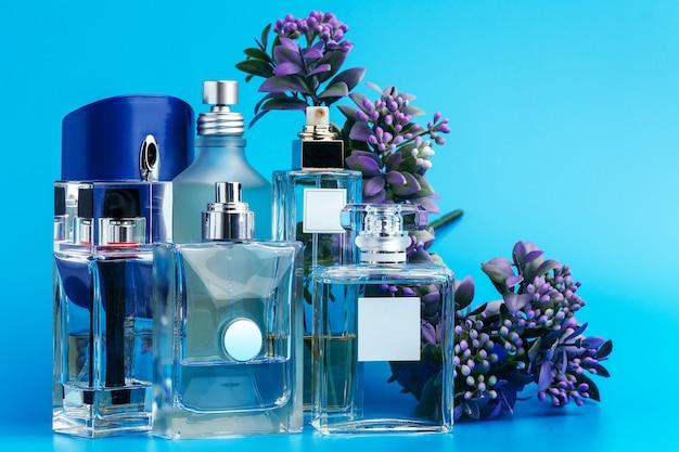 Parfumflesjes met bloemen op lichtblauw