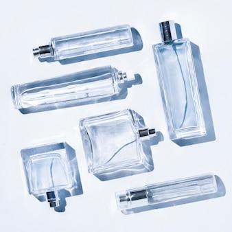 Parfumflesjes van lichtblauwe kleur. flatlay stilleven in de stijl van minimalisme op een achtergrond, schoonheid en mode, vierkante framing.