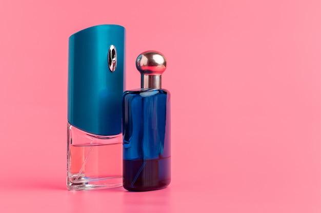 Parfumflessen op pastelkleur roze dichte omhooggaand