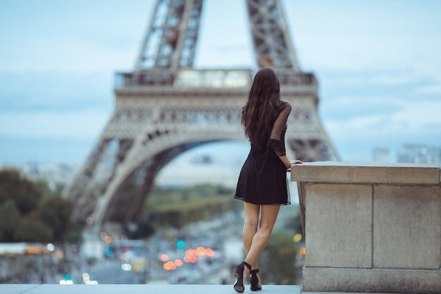 Parijse vrouw in de buurt van de eiffeltoren in parijs, frankrijk.
