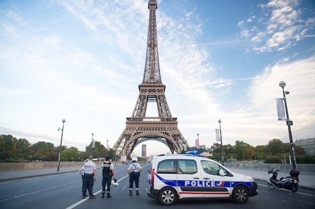 Paris, frankrijk - 29 september 2017: wegversperring op de achtergrond van de eiffeltoren. politieagenten en patrouillevervoer. politie auto en motor. beveiliging wegblokkade. controlepost voor het verkeer. stad op slot.