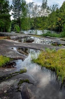 Park witte zee rotstekeningen in karelië. grote stenen, water en bos. prachtig landschap. verticaal.