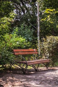 Parkbank, gemaakt van hout en gietijzer, zitten op de bank, zomervakantie