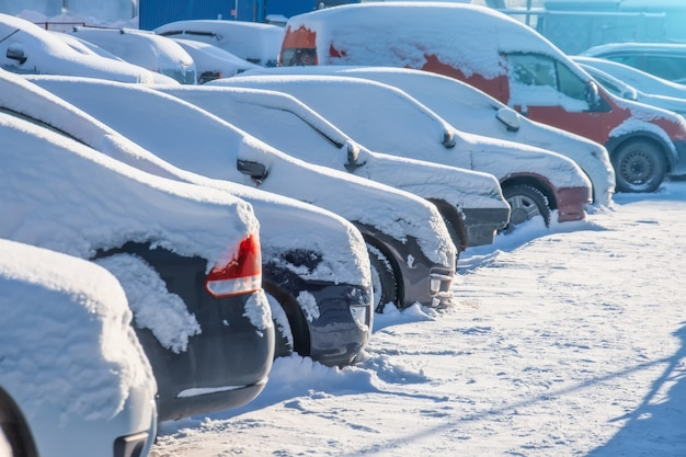 Parkeerplaats met zonovergoten auto's bedekt met verse sneeuw.