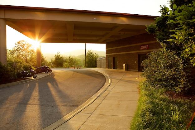 Parkeerplaats omgeven door groen en motorfietsen tijdens de zonsondergang