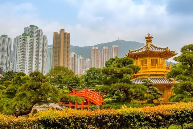 Parkeren in hongkong. gouden paviljoen omgeven door planten en bomen. wolkenkrabbers en bergen op de achtergrond