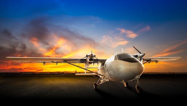 Parkeren vliegtuig op de landingsbaan van de luchthaven op de prachtige zonsondergang achtergrond