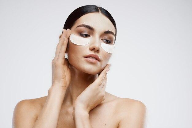 Parmantige brunette blote schouders patches gezichtsverzorging