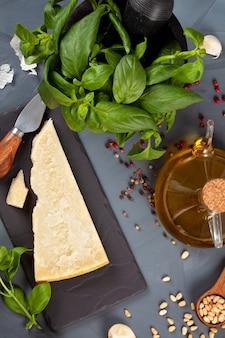 Parmezaanse kaas, olijfolie, basilicum, knoflook, pijnboompitten - verse ingrediënten voor het bereiden van pesto. italiaans keukenconcept