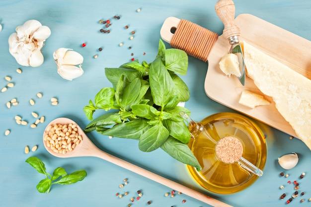 Parmezaanse kaas, olijfolie, basilicum, knoflook, pijnboompitten - verse ingrediënten voor het recept van de pesto. italiaans keukenconcept