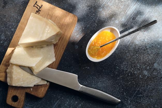 Parmezaanse kaas op houten snijplank met druiven bessen