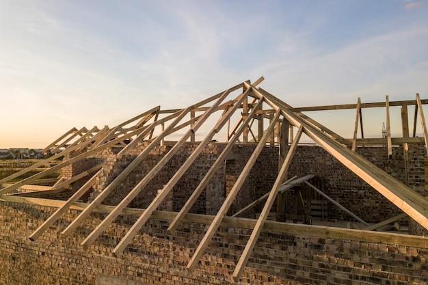 Particulier woonhuis met houten dakframe in aanbouw. onvoltooide bakstenen gebouw in ontwikkeling.