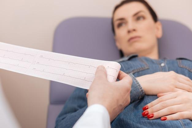 Particuliere succesvolle gekwalificeerde arts die de resultaten van het cardiogram bestudeert en de tekenen van hartpathologie opspoort terwijl hij zijn patiënt controleert