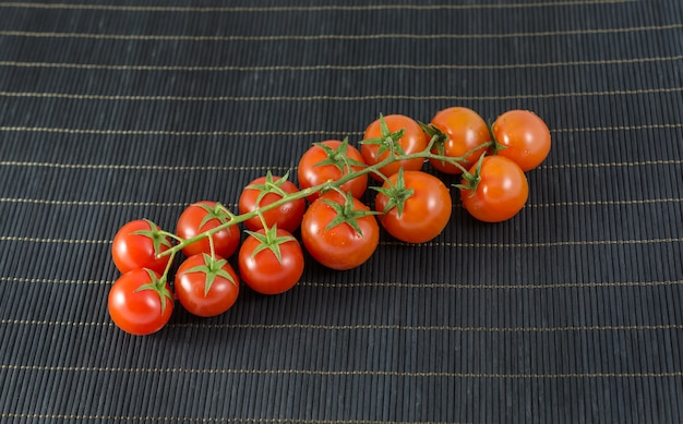 Partij baby tomaten op zwarte bamboe achtergrond