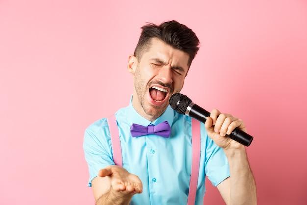 Partij en feestelijke evenementen concept. gepassioneerde zanger met microfoon en hand naar je wijzend, zingend over liefde, staande op roze achtergrond.