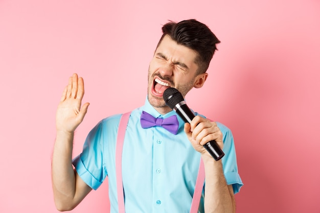 Partij en feestelijke evenementen concept. grappige kerel voert een lied uit, zingt karaoke in microfoon met zorgeloos gezicht, staande in vlinderdas en bretels op roze achtergrond.