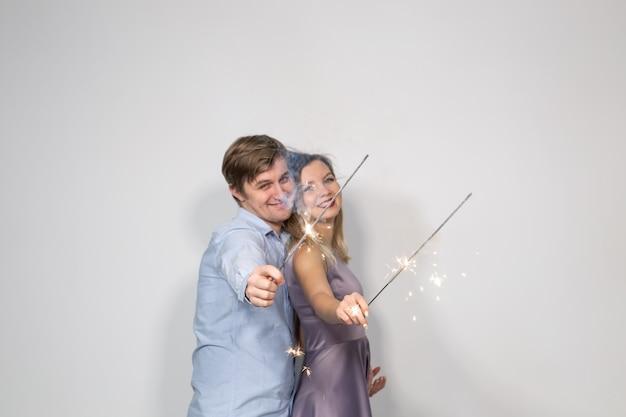 Partij, familie en vakantieconcept - jong paar dat hun verjaardag met wonderkaarsen viert