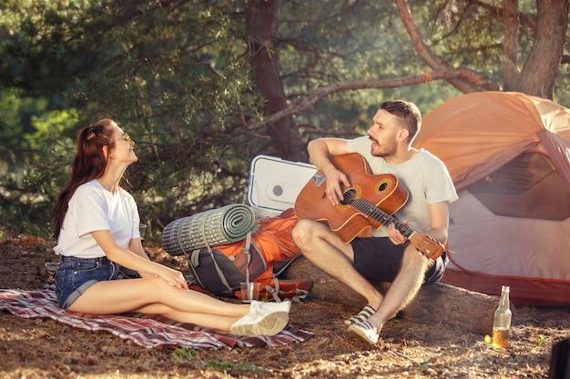 Partij, kamperen van mannen en vrouwengroep bij bos. ontspannen, een lied zingen tegen groen gras.
