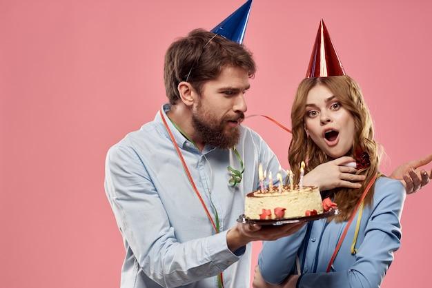 Partij man en vrouw met cake op roze muur zakelijke verjaardag.