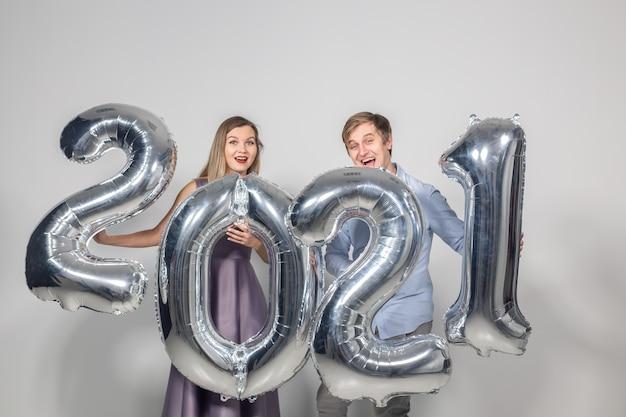 Partij, mensen en nieuwjaarsvakantieconcept - vrouw en man vieren oudejaarsavond 2021.