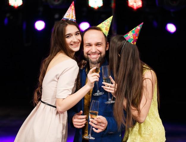Partij, vakantie, feest, nachtleven en mensenconcept - glimlachende vrienden met glazen champagne in club